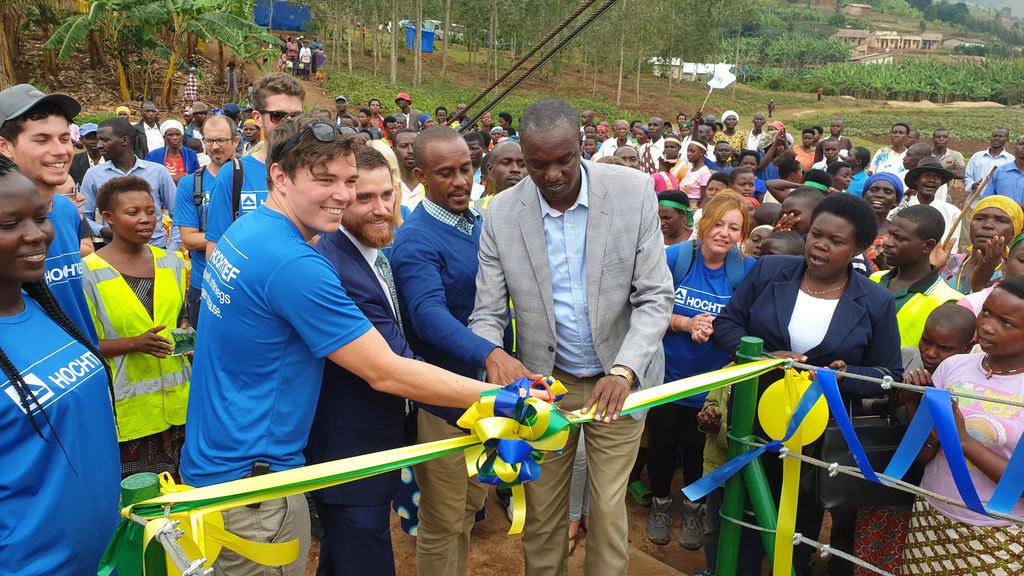 """2019: Rufuha-Brücke in Ruanda - In den Landesfarben gestrichen, leuchtet die 34 Meter lange """"Rufuha Bridge"""" von weitem. 2019 wurde die Brücke fertiggestellt und mit einer großen Feier eröffnet. Mit im Team: Mitarbeiter von HOCHTIEF, ACS und CIMIC."""